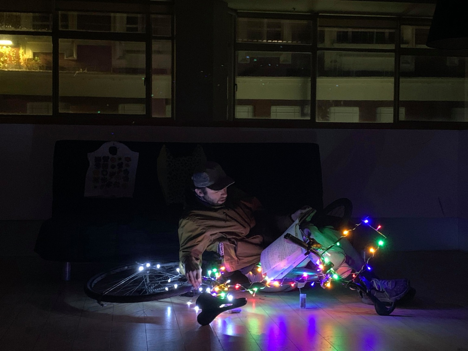 A figure who is tangled within the frame of a bicycle reads from a large notebook on the floor of a darkened space. The bicycle is festooned with decorative lights.