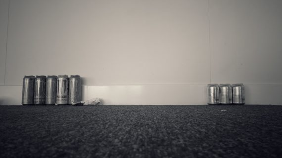 black floor with white wall with two sets of drinks cans