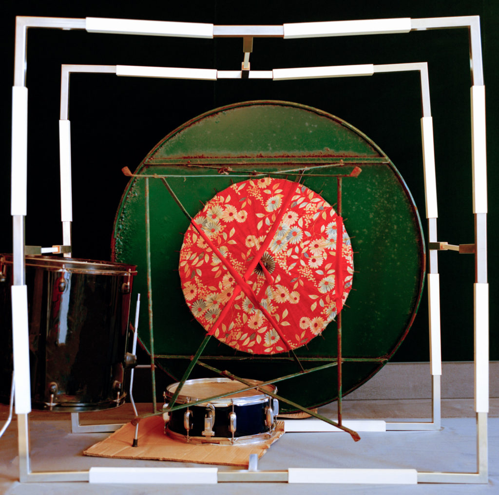 Still life photograph including square metal frames, two drums, a large green metal disc and a red floral patterned parasol
