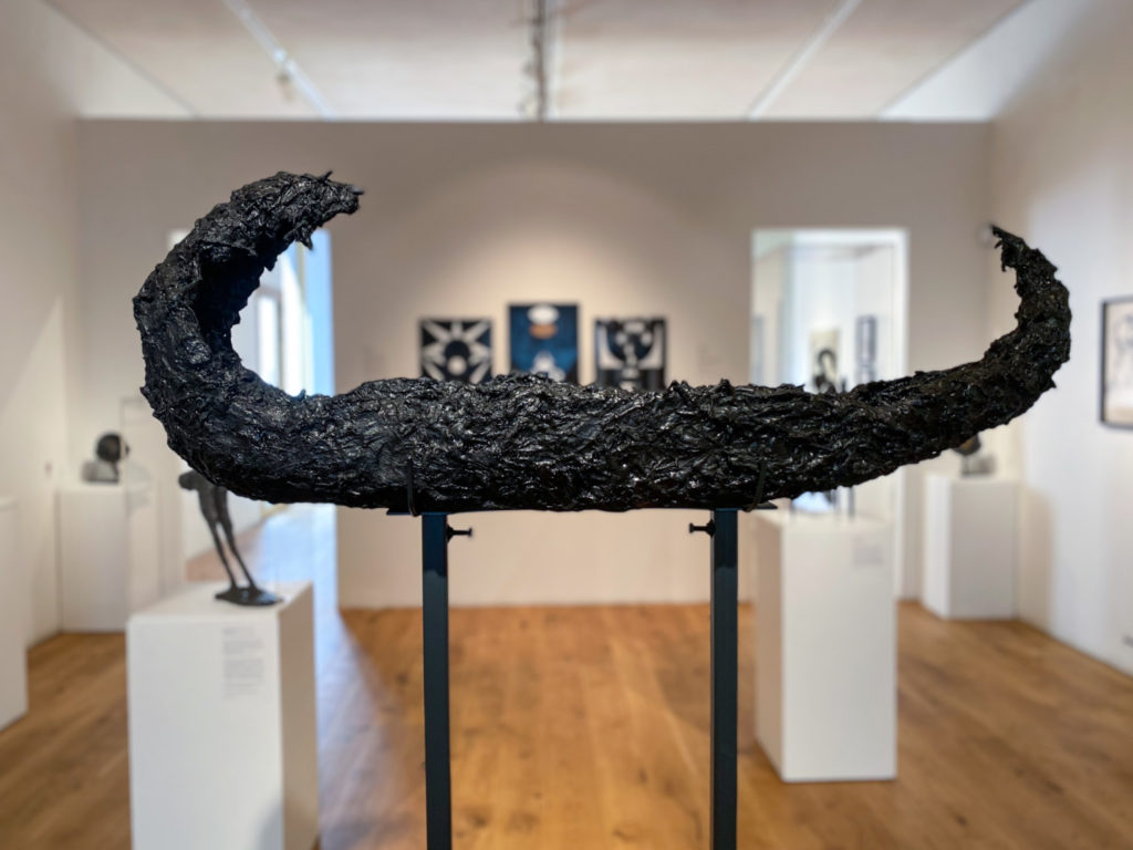 Long thin black textured sculpture with upward curved tips, elevated on a black metal structure
