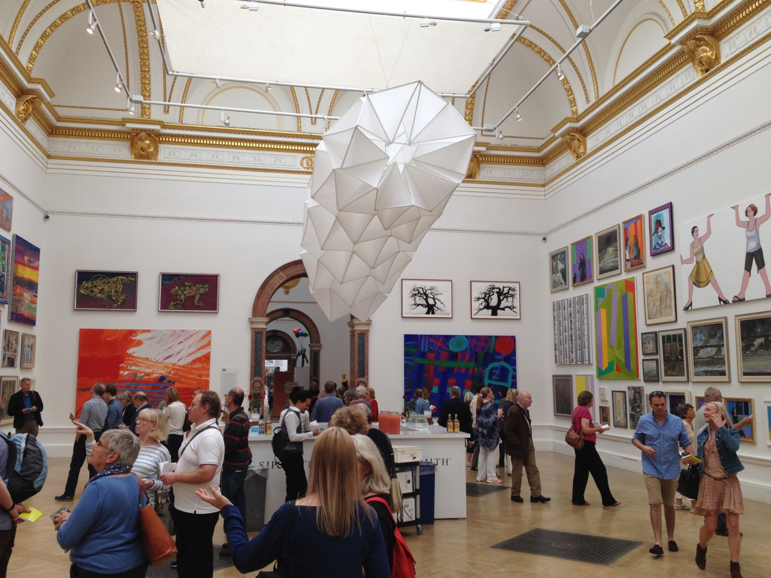 A busy gallery space with may artworks lining the walls and a large sculpture suspended from the ceiling.