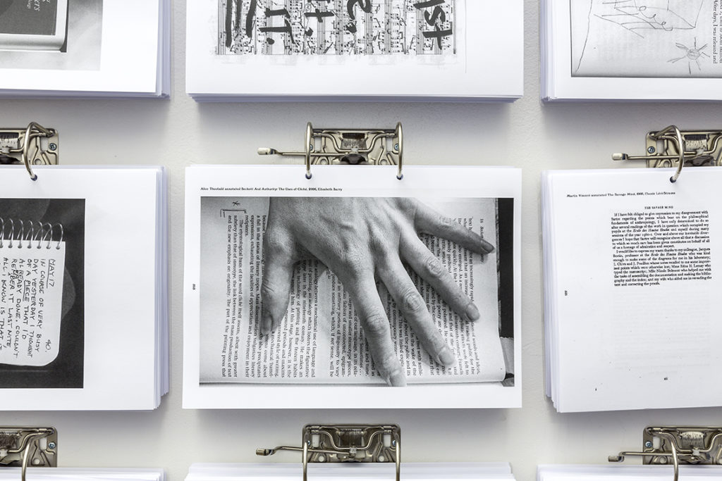 A grid of black and white photocopies hanging from metal ring binder hoops. The central photocopy shows a hand on top of a page of a book