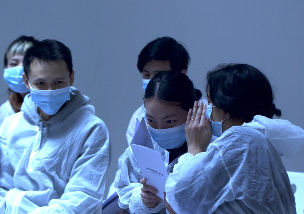Five figures are dressed in hazchem suits and masks. One figure is whispering in the ear of another figure.