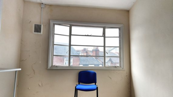 blue chair in front of window looking out to built environment