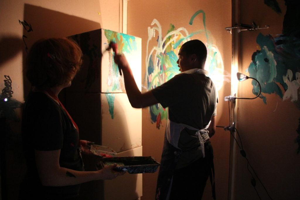 A person painting directly onto the walls on the inside of a room whilst an assistant holds a paint tray.