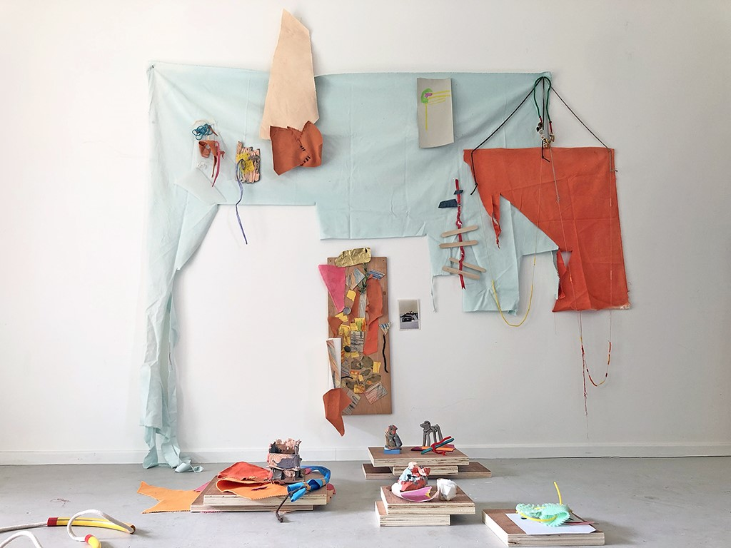 Wall and floor installation made from various materials including pale blue and orange fabric, paper, rope, plastic and squares of plywood