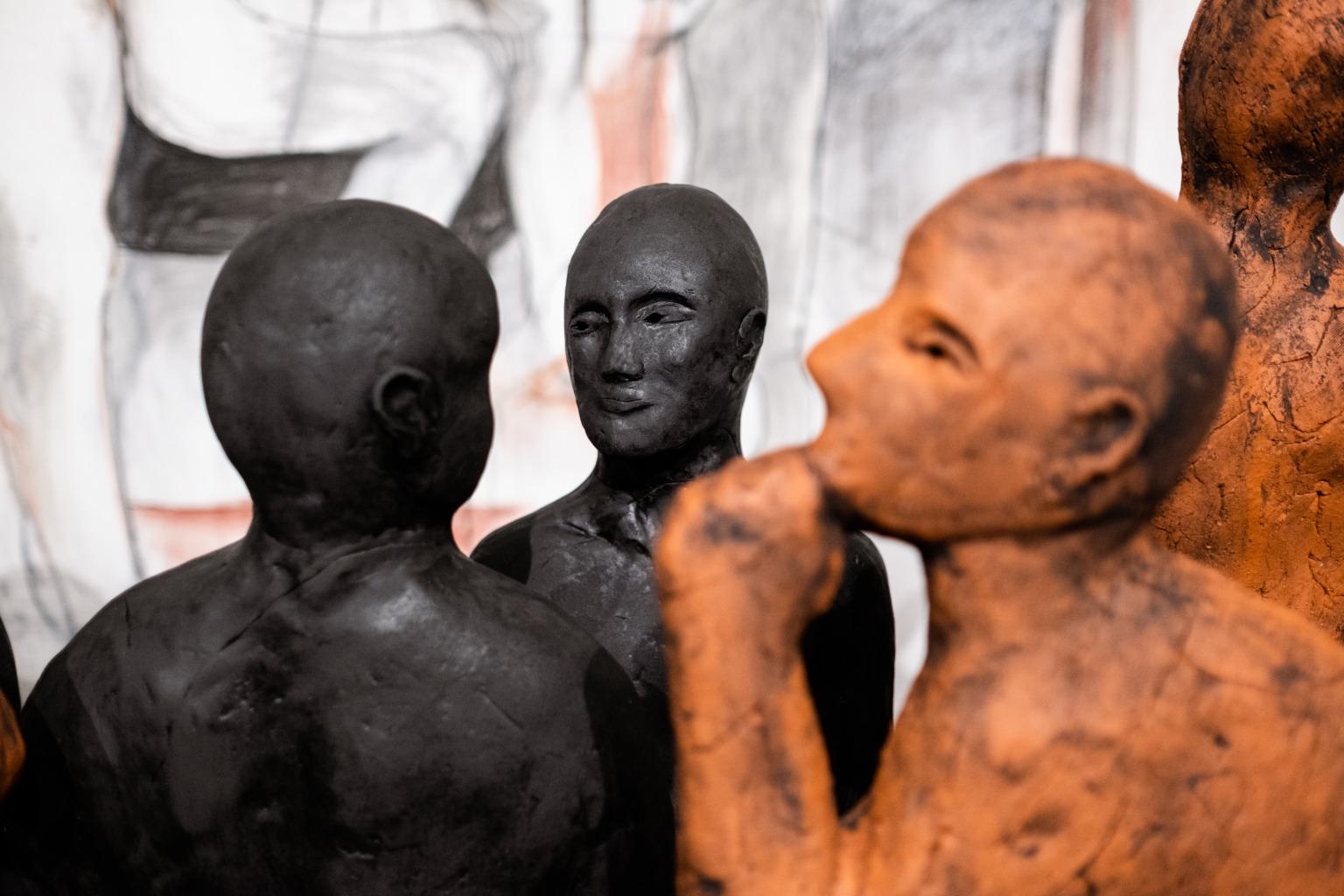 Three sculptural human figures.