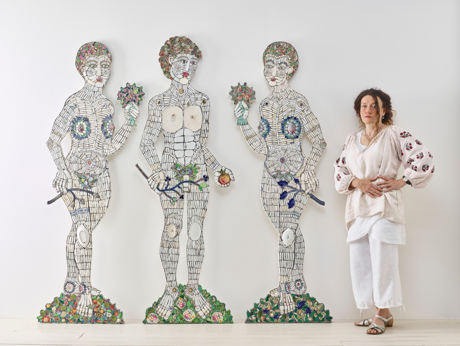 Three life size ceramic figures, with the artist stood to the right of them.