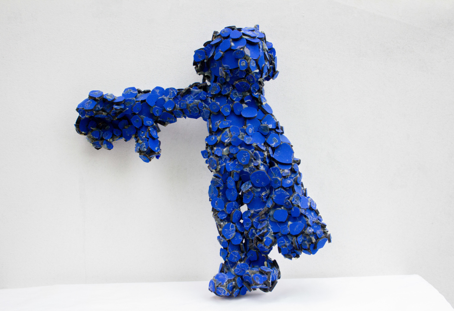 A figure made of many blue neoprene rubber discs glued together