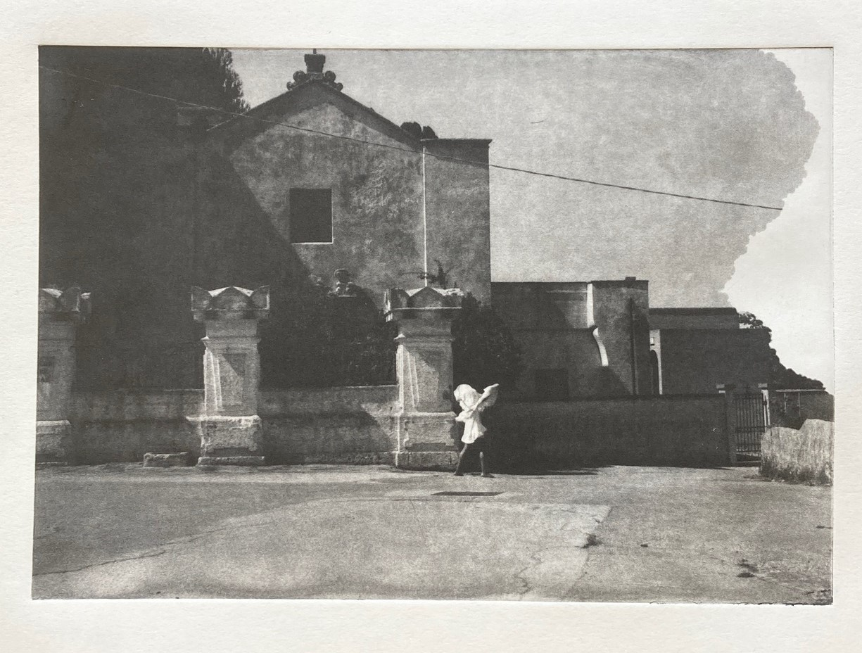 Black and white print depicting a building standing behind a wall and 3 large columns. A figure dressed in a white sculptural top that covers their head stands in front of the wall.