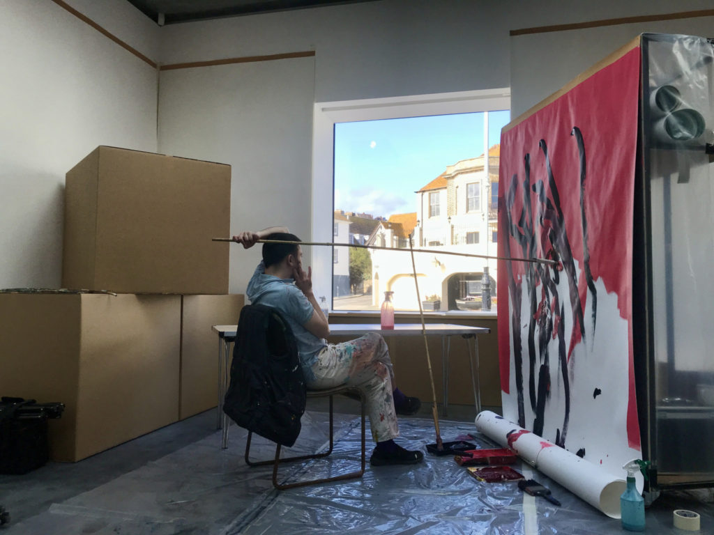 A seated artist paints a painting with a long-handled brush