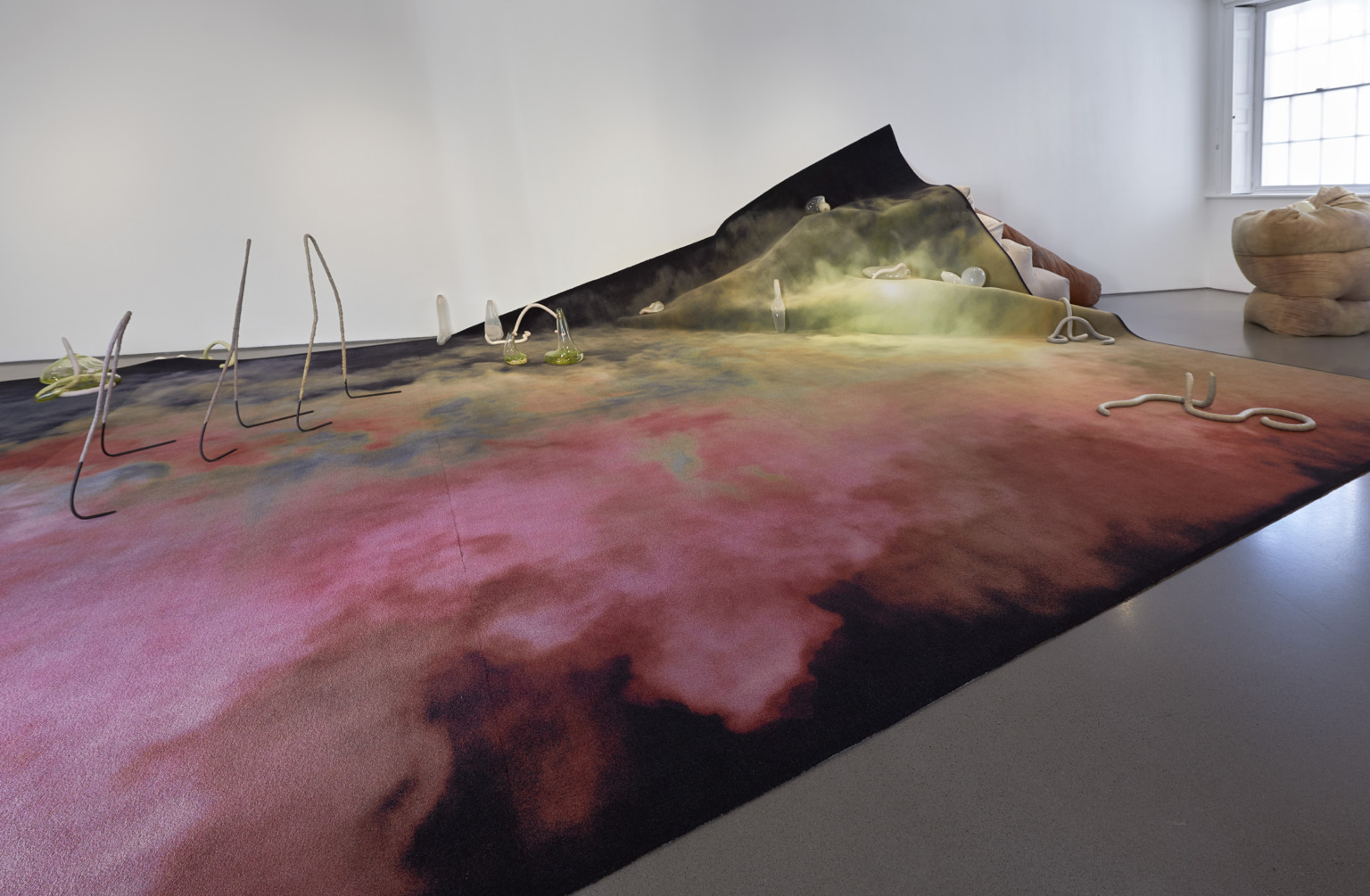 Floor-based sculptural installation including a large rug with pink, yellow and blue cloud-like washes of colour, and small sculptures on top of it