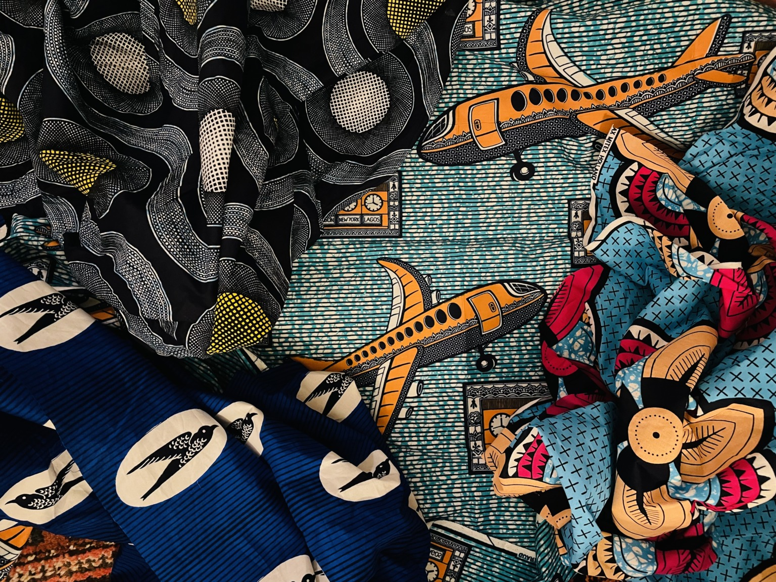 Close up of various brightly coloured African printed fabrics, including one with a pattern of an orange aeroplane, another with a bird, and others with abstract patterns.