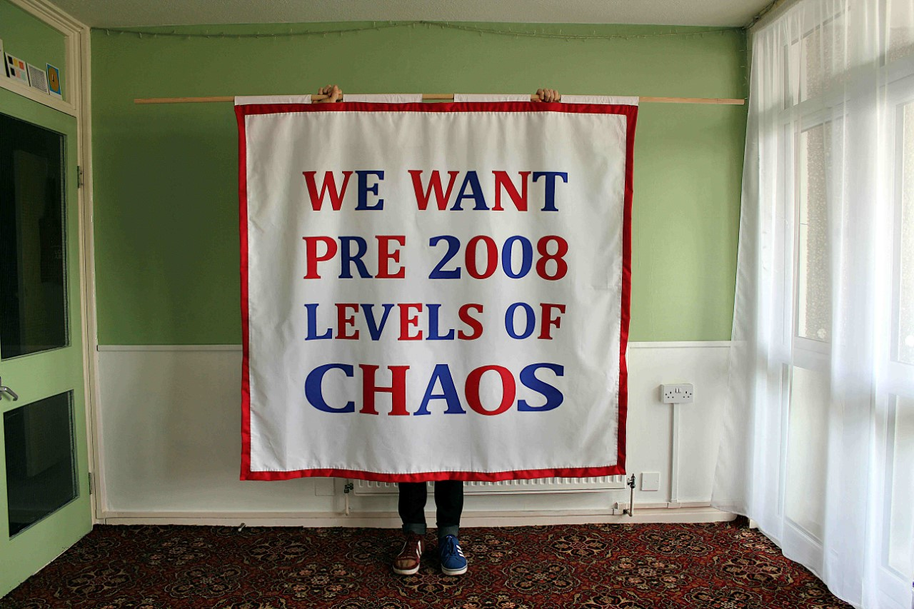 A square white banner with the words 'We want pre 2008 levels of chaos' in red and blue lettering on a white background. A person is holding the banner with only their hands and lower legs visible. They are in a small room with green walls, patterned floral carpet and net curtains.