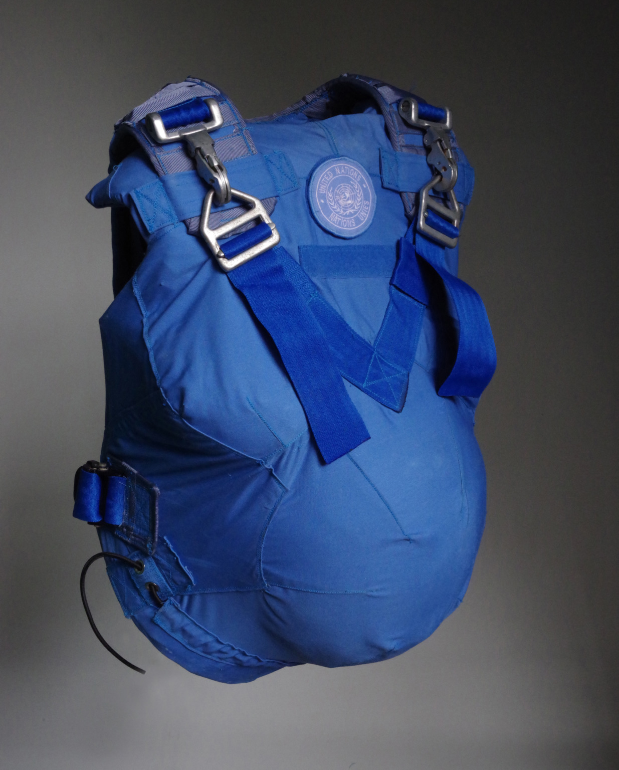 A blue fabric covered sculpture resembling a sleeveless jacket with space for a pregnant belly, with shoulder straps and metal buckles. On the chest is a United Nations badge