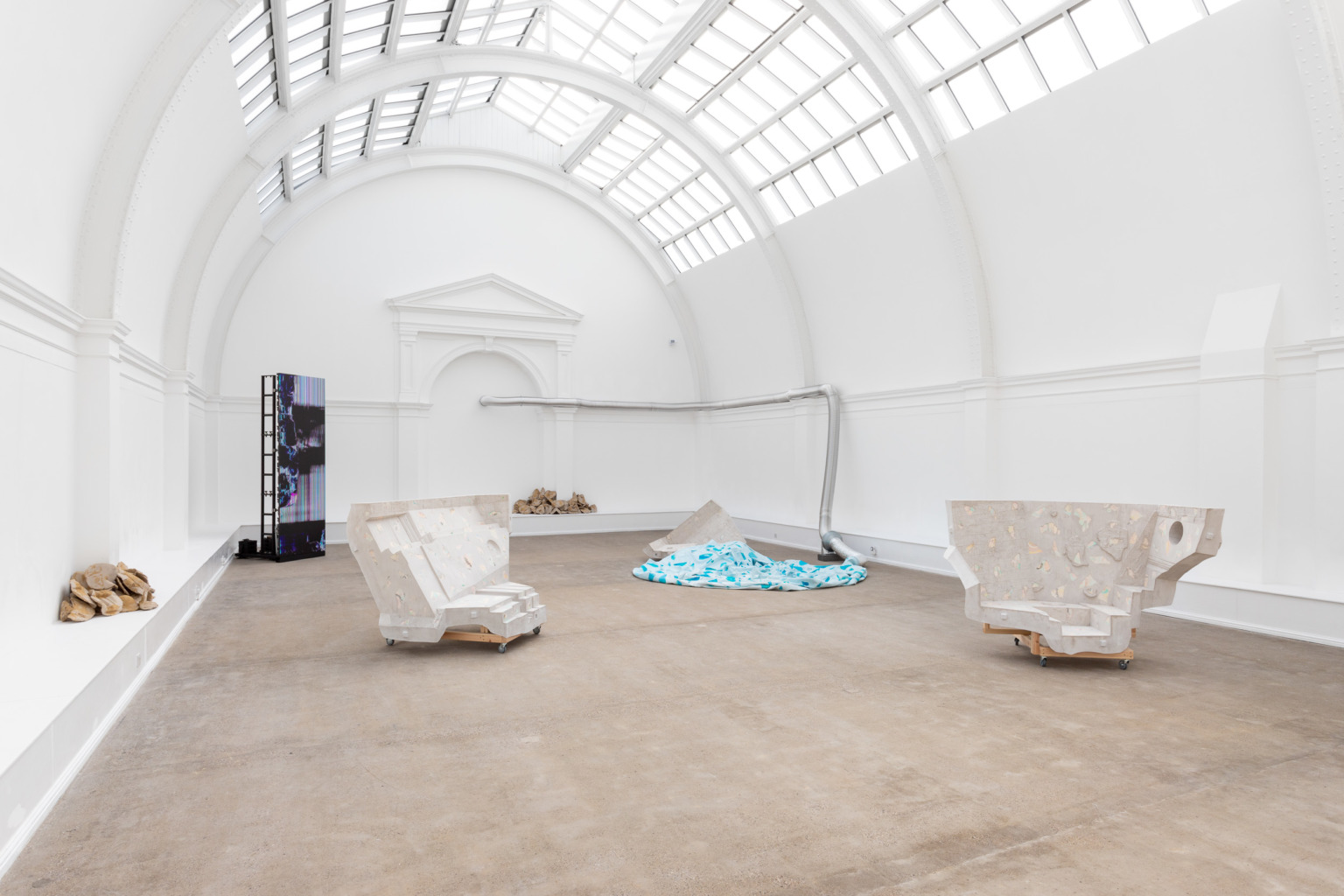 Six sculptures in a white gallery space with a glass arched roof.