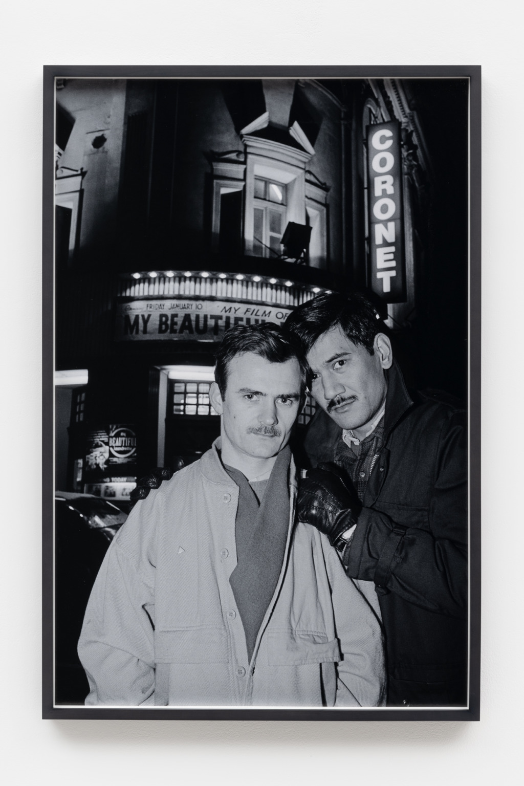 Black and white photograph of two men looking into the camera, standing with their heads touching, in front of a theatre with a lit sign that reads 'Coronet'. Above the door is a sign that reads 'My beautiful-'. The men are dressed in outdoor jackets and scarves. One has his hands in his pockets, the other rests his gloved hands on that man's shoulders.